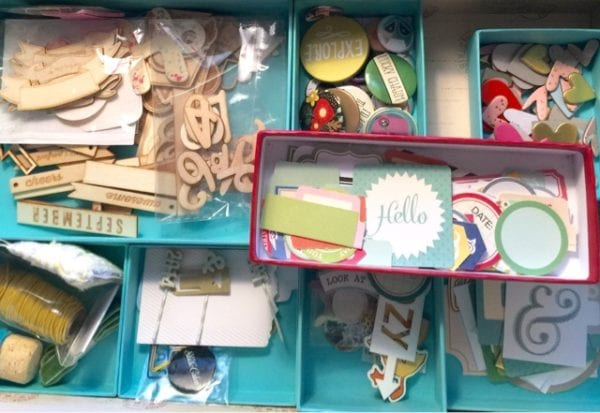 While papers and journal cards are organized by color, I don't use that for my elements.  I use little boxes and lids to organize my ellies by type.  I found I will most often look for a certain type of ellie: a  label, or heart or star- and having them all in one place makes it easier to find.